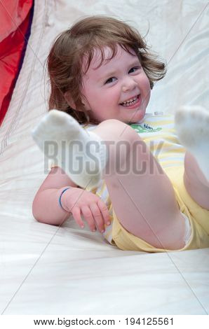View of Young happy girl child riding inflatable slide outdoors on a warm summer day.