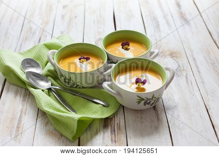 Puree soup, made from orange pumpkin, sweet potatoes and carrots, served with sour cream