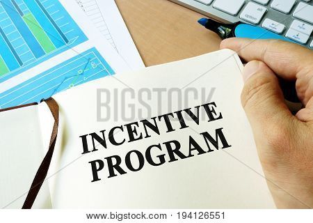 Hands holding book with title Incentive program.