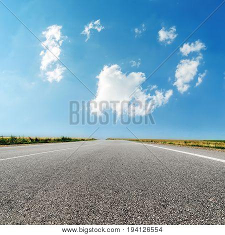 asphalt road closeup and clouds in blue sky