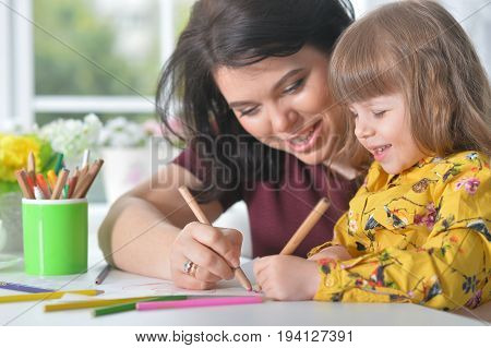 Portrait of a mother and daughter drawing picture