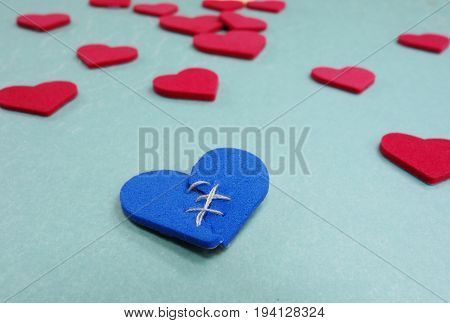 Blue stitched broken heart and assorted red hearts