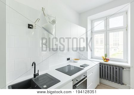 Kitchen with white tiling simple furniture and window