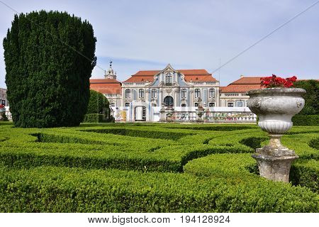 Queluz Portugal - June 3 2017. Neptune gardens (baroque) and one of the facades of the Queluz Royal Palace. Formerly used as the Summer residence by the Portuguese royal family