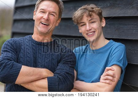Portrait shot of an attractive, successful and happy middle aged man father male arms folded with his teenage boy son outside laughing teen, wearing a blue sweater and t-shirt