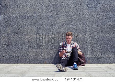 Mid shot of carefree student leaning on wall while listening to music. Casual man using telephone
