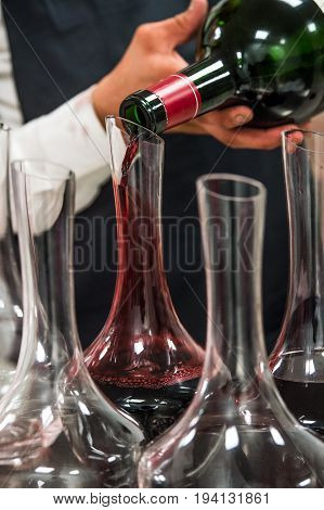 Sommelier at work, pouring wine to decanter while standing near the wine shelf, Luxury Diner
