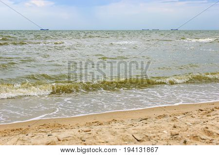 Seascape with ship in the distance and cloudy sky. Soft sea ocean waves wash over golden sand background. Beautiful seascape with water splashes. Selective focus on the splash