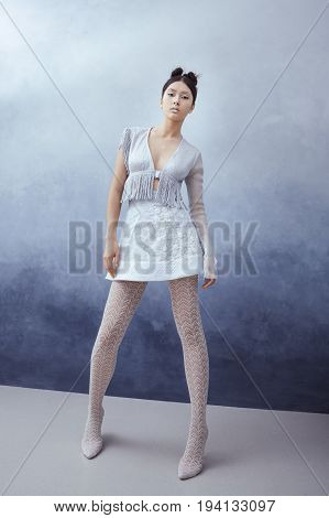 Futuristic fashion young woman. Beautiful young multi-racial asian caucasian model girl in silver urban clothes with conceptual hairstyle and make-up against textured blue wall in full lenght. Sci-fi poster style.
