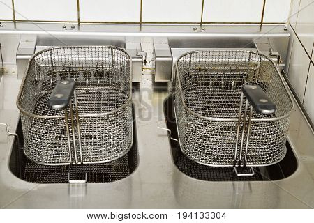 Two metal deep fryers with grips in kitchen of a restaurant, bistro or cafe.