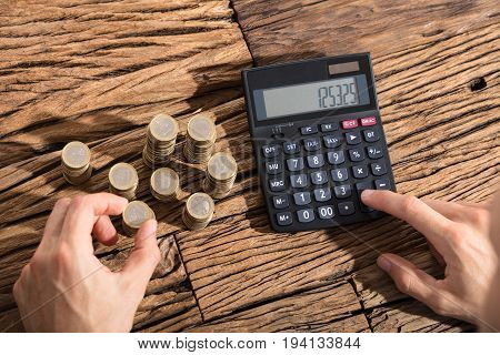 Close-up Of A Person Calculating Coins Through Calculator On Wooden Desk