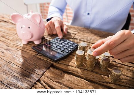 Close-up Of A Business Person Counting Coins Using Calculator With Pink Piggybank Over The Desk