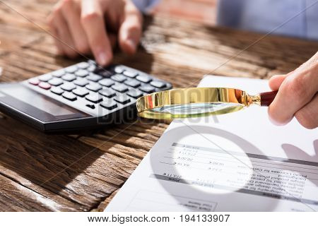Close-up Of Accountant Using Magnifying Glass And Calculator While Calculating Finance