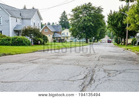 Kane USA - July 21 2014: Residential neighborhood in city with rough roads and streets and houses