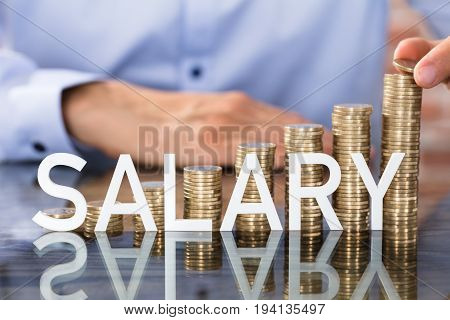 Person Placing Coin Over The Increasing Stack Of Coins With Word Salary