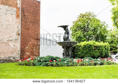 Frederick USA - May 24 2017: Fountain in downtown city in Maryland with brick building exterior and flowers