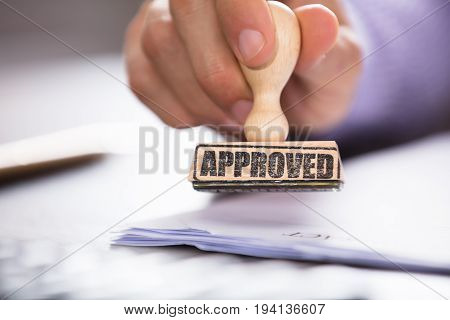 Close-up Of A Person Hand Holding Approved Stamp On Document Over The Desk In Office