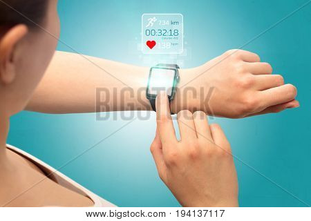 Female hand with smartwatch and running concept above.