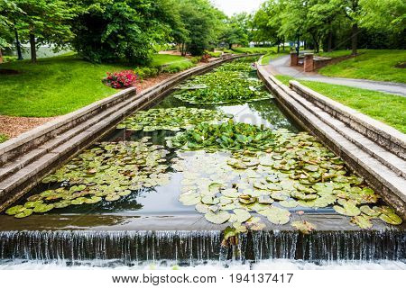 Carroll Creek in Frederick Maryland city park with canal and fountain waterfall and flowers in summer