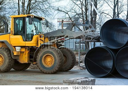 forklift distributes plastic pipes of large diameter