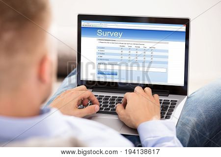 Businesswoman With Laptop On His Lap Filling Survey Form