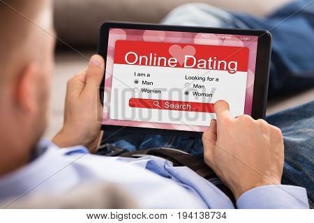 Close-up Of A Man Browsing Online Dating Website On Digital Tablet