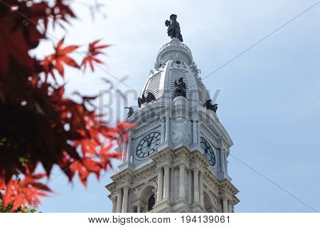 Top of City Hall and blur of red japanese maple tree in downtown Philadelphia, Pennsylvania, USA. Copy/text space.