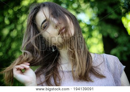 Portrait of a young beautiful woman with a hairstyle on the face in the Park. Windy day. Background Bokeh