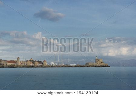 Medieval fortress of Saint Nicholas now the site of a lighthouse in Mandraki Harbour Rhodes Greece with the mountains of Turkey in the distance