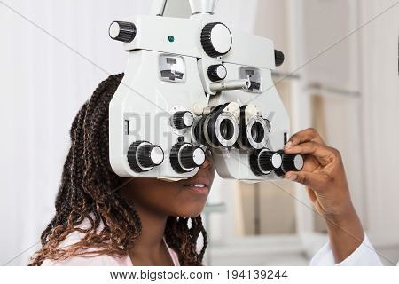 Close-up Of An Optometrist's Hand Adjusting Phoropter For Patient In Clinic