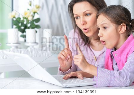 Mother  with her little daughter using laptop