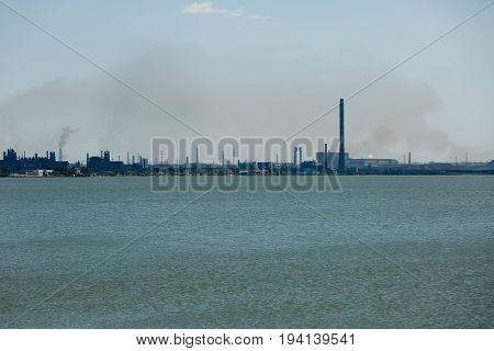 Big steel factory metallurgical plant with sea harbor and lots of pipes throwing dark dirty smoke and dust in the atmosphere. Ecological air and water pollution problems concept
