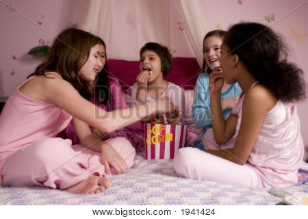 Five friends enjoying popcorn together at a slumber party. poster