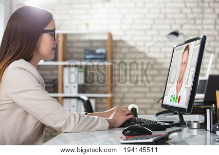 Young Businesswoman Doing Video Conference On Computer At Workplace In Office