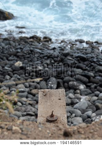 wooden ledge above rocks and ocean water
