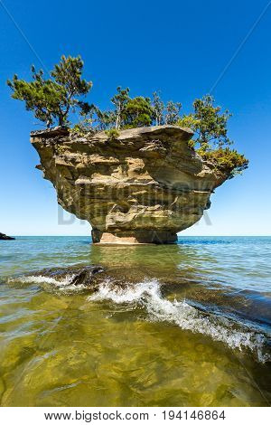 A Lake Huron wave splashes over a rock at Turnip Rock near Port Austin Michigan. Clear waters allow a view underwater