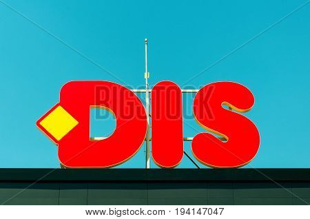 Red commercial sign of supermarket DIS placed on the roof top with blue sky background. July - 06. 2017. Novi Sad, Serbia. Editorial image.