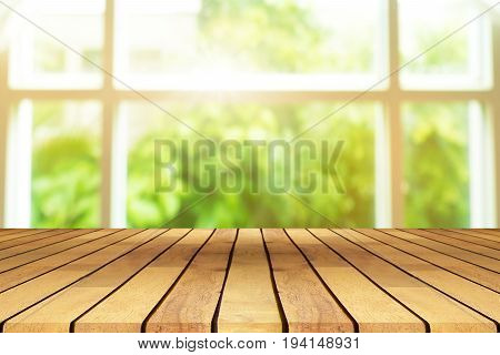 Perspective wooden table on top over blur background view from the coffee shop window can be used mock up for montage products display or design layout.