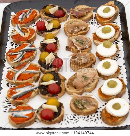 Assortment of canapes on plate. Toasts fish eggs tomatoes for aperitif time