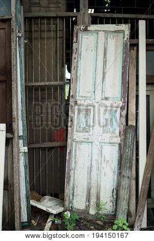 Old Wooden Door Leaning Against Old Rusty Metal Bar Wall