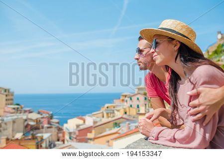 Tourists looking at scenic view of Riomaggiore, Cinque Terre, Liguria, Italy