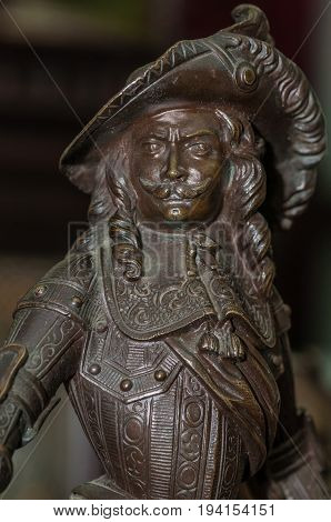 Moscow, Russia - March 19, 2017: Collection antique statuette, portrait of a bronze musketeer in hat with a pen close-up. A graceful rare French thing for collecting and decorating a classic interior.