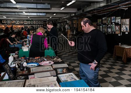 Moscow, Russia - March 19, 2017: Showroom is a covered antique market with a lot of rare antiques, collectibles items and art. Possible buyer in the foreground chooses items for his collection.