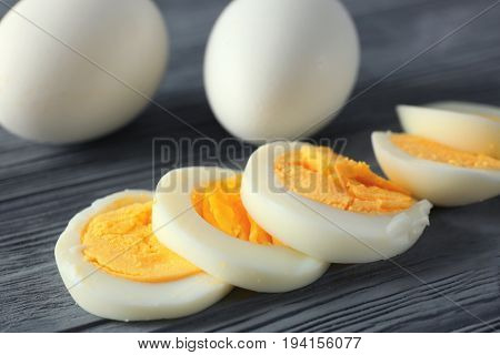 Sliced hard boiled eggs on wooden background. Nutrition concept