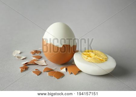Hard boiled eggs and shell on grey background. Nutrition concept