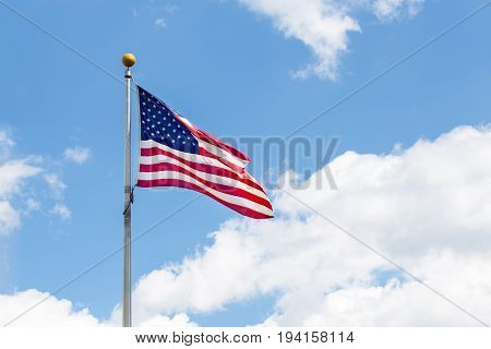 The american Flag waving over blue sky.