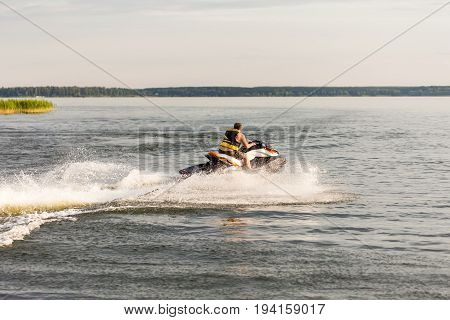 A man driving a jet ski , stunting and making spray of water drops.