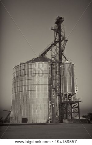 newly constructed metal grain silo and elevator against clear sky, black and white, sepia toned image