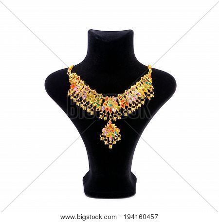 Colorful golden necklace East stile on black mannequin isolated on white background