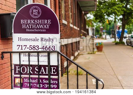Harrisburg USA - May 24 2017: Pennsylvania capital city houses with Berkshire Hathaway for sale sign in downtown by sidewalk street